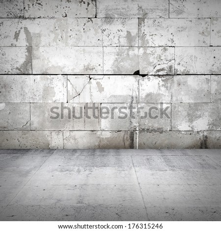 Interior with old damaged stone wall and concrete floor - stock photo