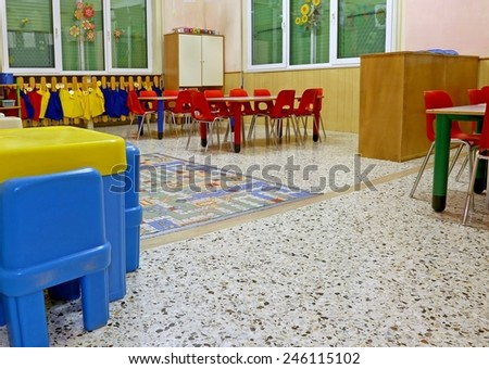 interiors of a nursery class with coloredchairs and  drawings of children hanging on the walls - stock photo
