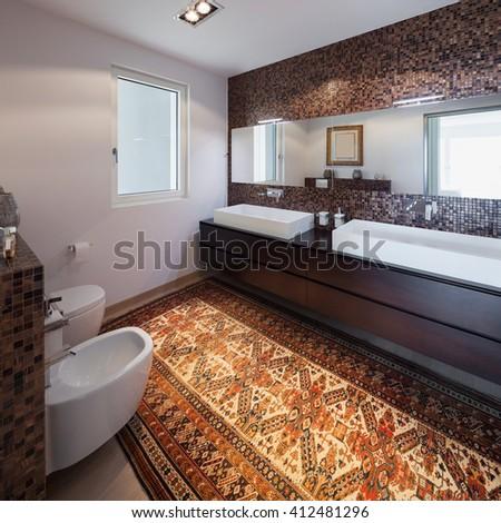 Interiors of new apartment, bathroom, tiled walls - stock photo