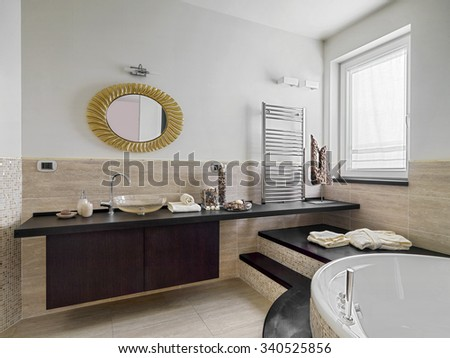 internal view of a modern bathroom with a bathtub in the corner and two steps - stock photo