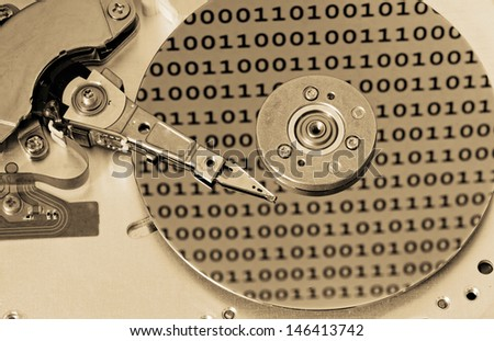 Internals of a computer harddrive with binary number reflections with sepia colors (HDD, winchester) - stock photo