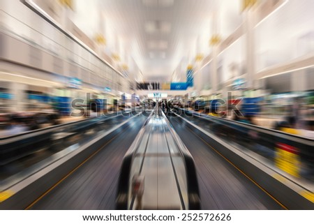 International airport with unrecognizable people moving on treadmills with motion blur. Radial zoom defocused editing. Social gathering and globalization concept. - stock photo