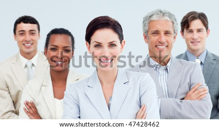 International business people standing with folded arms smiling at the camera - stock photo