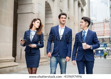 International business team walking outdoor - stock photo