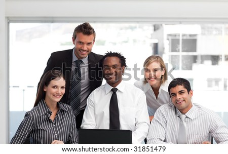 International business team working in an office looking at the camera - stock photo