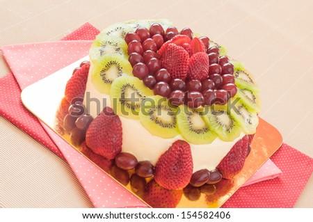 International cuisine desserts, tasty cake with cream decorated with fresh strawberries, grape and kiwi. - stock photo