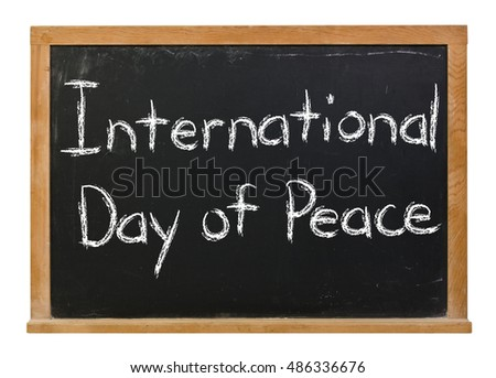 International Day of Peace written in white chalk on a black chalkboard isolated on white