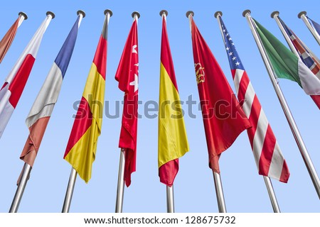 International flags in a row against a blue sky. Clipping path - stock photo