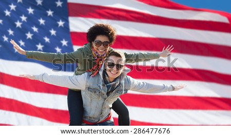 international friendship, freedom and people concept - happy teenage couple in shades having fun over american flag background - stock photo