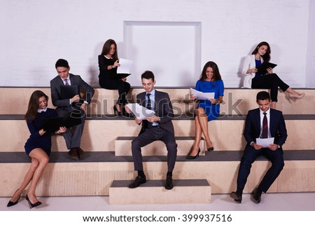 International group of a young men and women in corporate clothes professionals bookkeepers by using paper documents preparing to interviews with the personnel manager of a large successful company - stock photo
