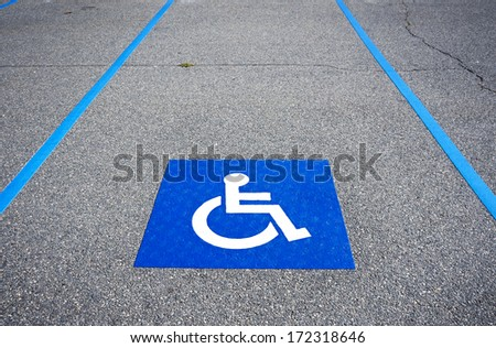 International handicapped symbol painted in bright blue on a shopping center parking space. The space is clearly marked on either side with additional white diagonal stripes. - stock photo