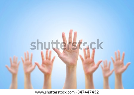International Human Rights conceptual idea: Many people blur hands raising upward on blue sky background w/ world map showing participation in social, economic, politic areas: Volunteer day concept    - stock photo
