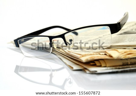 International News, newspapers with black glasses on top - stock photo