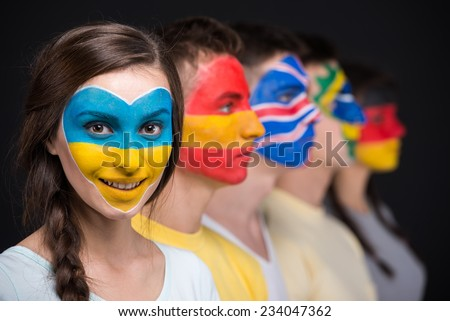 International team. Five  young people with national flags painted on the faces.