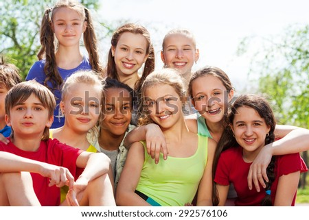 International teenagers sitting close in park - stock photo