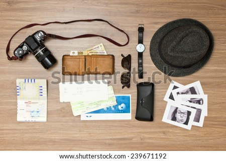 International travel background with a retro or vintage touch. Items include an old photo camera, passport, wallet with currency, airplane ticket, hat, sunglasses and black and white photos - stock photo