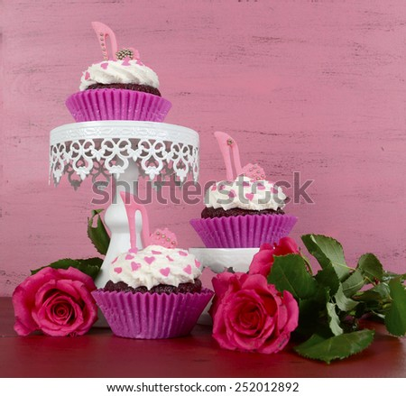 International Womens Day, March 8, cupcakes with high heel stiletto fondant shoes on vintage pink wood background, on cake stands with roses. - stock photo