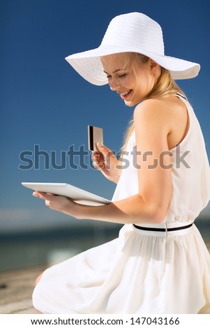 internet and lifestyle concept - beautiful woman in hat doing online shopping outdoors
