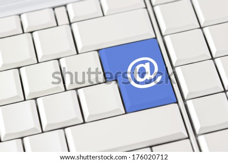 Internet domain, website and email icon on a single blue key on a computer keyboard with white keys conceptual of online communication, a website domain and contact via email. - stock photo