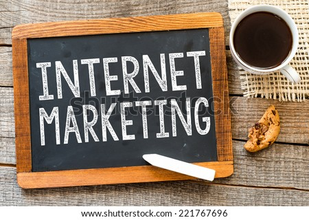 Internet marketing handwritten with white chalk on a blackboard, cup of coffee and biscuit on a wooden background  - stock photo