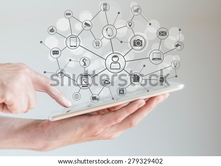 Internet of Things concept (IoT) with male hands holding tablet or large smart phone in order to connect various devices and smart machines. - stock photo