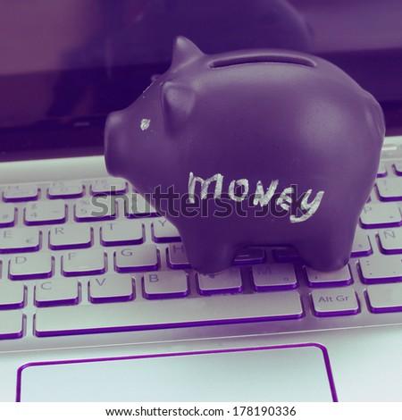 internet shopping concept - black piggy bank on laptop keyboard - stock photo