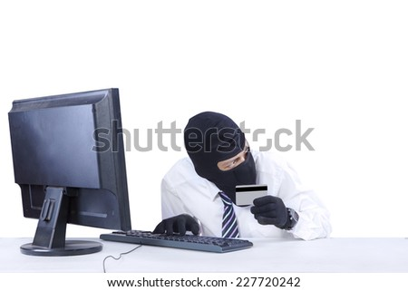 Internet Theft - businessman wearing a mask and holding a credit card while sat behind a computer - stock photo