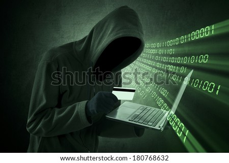 Internet theft concept - Man holding credit card with laptop on his hand - stock photo
