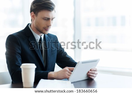 Internet user. Cheerful young man using digital tablet while coffee break in office  - stock photo