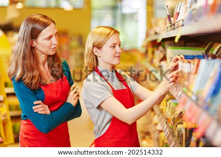 Internship organizing shelves in supermarket under supervision of the store manager - stock photo