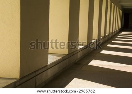Interplay of sunlight and shadow along passageway outside university building - stock photo