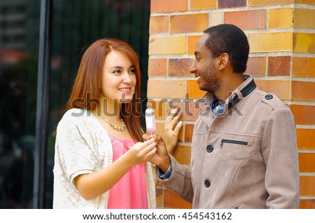 Interracial charming couple wearing casual clothes interacting happily and sharing an ice cream - stock photo