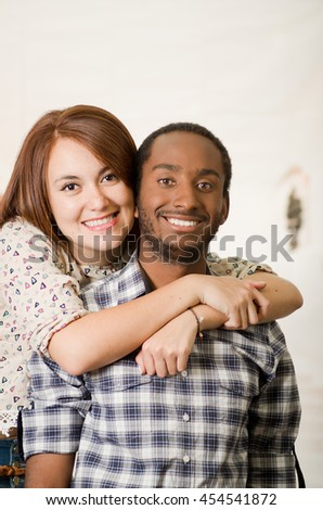 Interracial charming couple wearing casual clothes posing embracing friendly and smiling, white studio background - stock photo