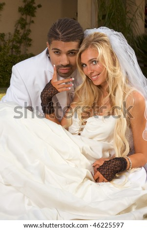 Interracial couple outdoors. Smiling laughing newlywed young Caucasian woman and mid aged ethnic black man of African American and Italian ethnicity sitting on lawn in front yard - stock photo