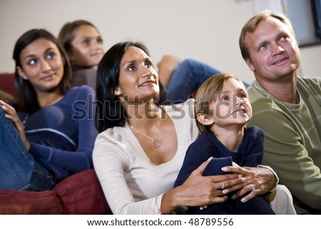 Interracial family of five sitting together on sofa looking up watching TV - stock photo