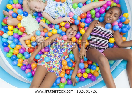 Interracial Group of girls, blond and African American children having fun laughing playing colorful plastic balls in a ball pit - stock photo