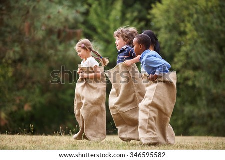 Interracial group of kids competing at a sack race in summer - stock photo