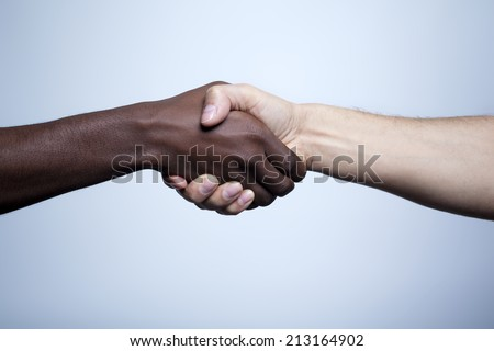 Interracial handshake on gray background - stock photo