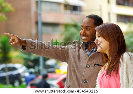 Interracial happy charming couple wearing casual clothes interacting for camera in outdoors urban environment - stock photo