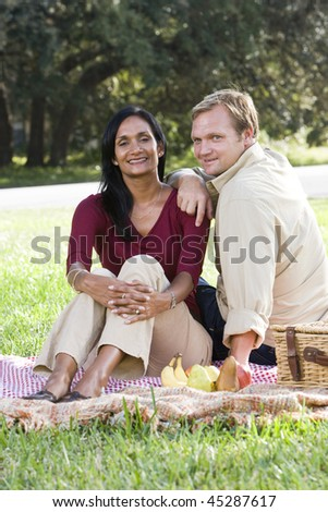 Interracial mid-adult couple sitting on picnic blanket in park on sunny day - stock photo