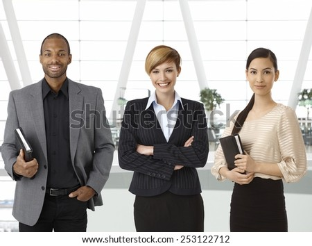 Interracial team of businesspeople standing for portrait in business hallway, smiling. - stock photo