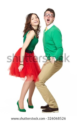 Interracial weird nerd couple dancing together. Excited caucasian young man wearing eyeglasses and smiling asian woman wearing 50 style clothes. Fifties nerd concept - stock photo