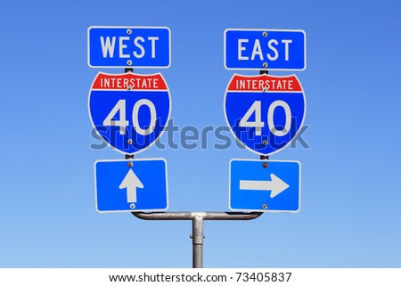 Interstate I 40 east and west road signs with blue sky background - stock photo