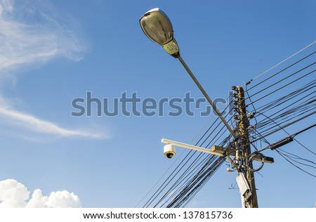 Intertwining of many electrical wires on poles and street lighti - stock photo
