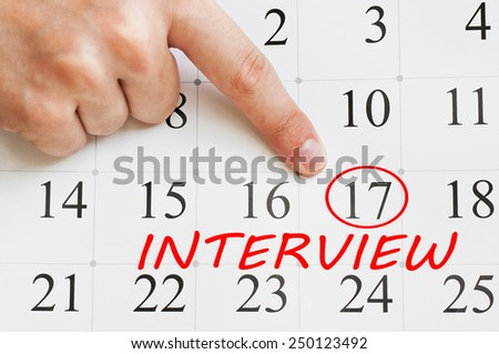 Interview date is circled on a calendar page with a finger pointing on it - stock photo