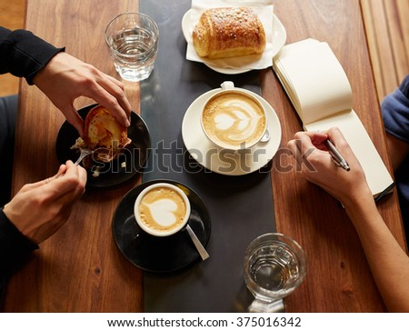 Interview in a cafe with coffee and pastry - stock photo