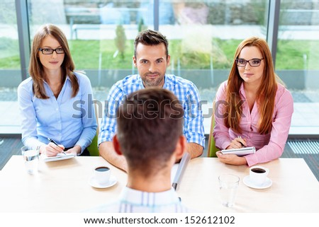 Interview. Three corporate people Interview young man - stock photo