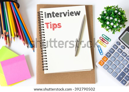interview tips text message on white paper and office supplies, pen, paper note, on white desk , copy space / business concept / view from above, top view - stock photo