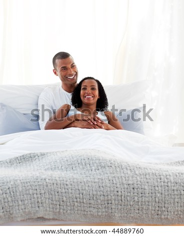 Intimate couple cuddling lying on their bed. Concept of love.