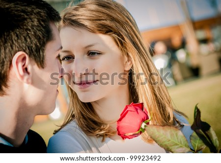 Intimate moment - young couple, woman holding red rose - stock photo